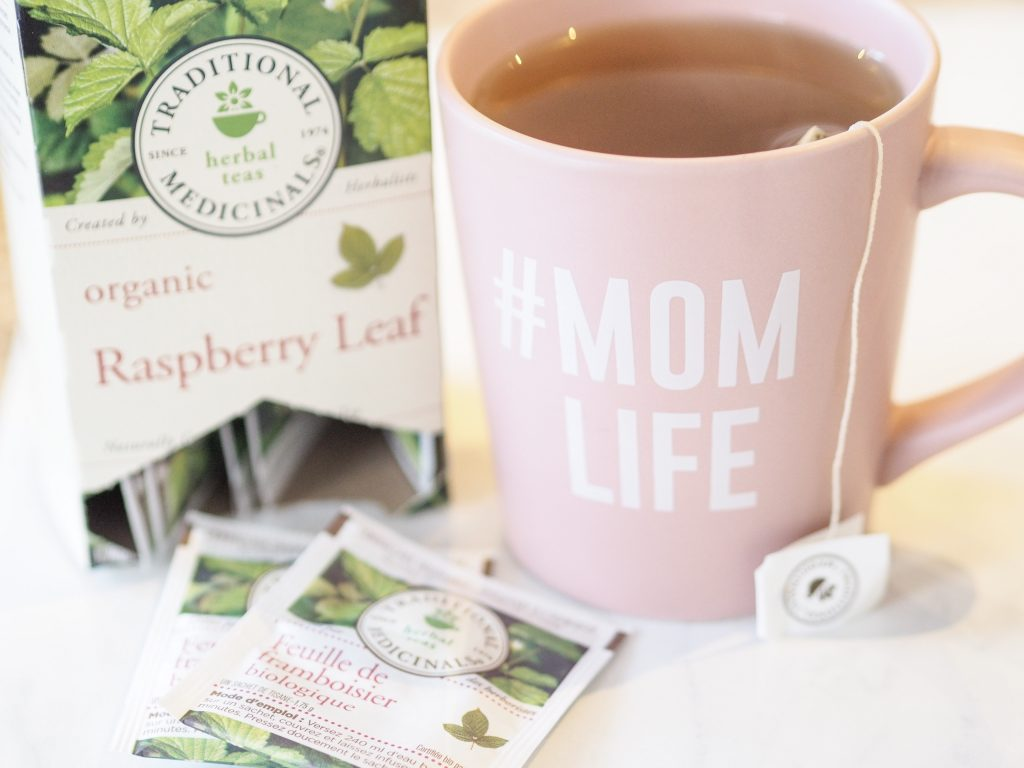 Traditional Medicinals Herbal TeasOrganic Raspberry Leaf Tea box and two tea packets. Pink #Momlife tea mug with organic raspberry tea steeping inside.