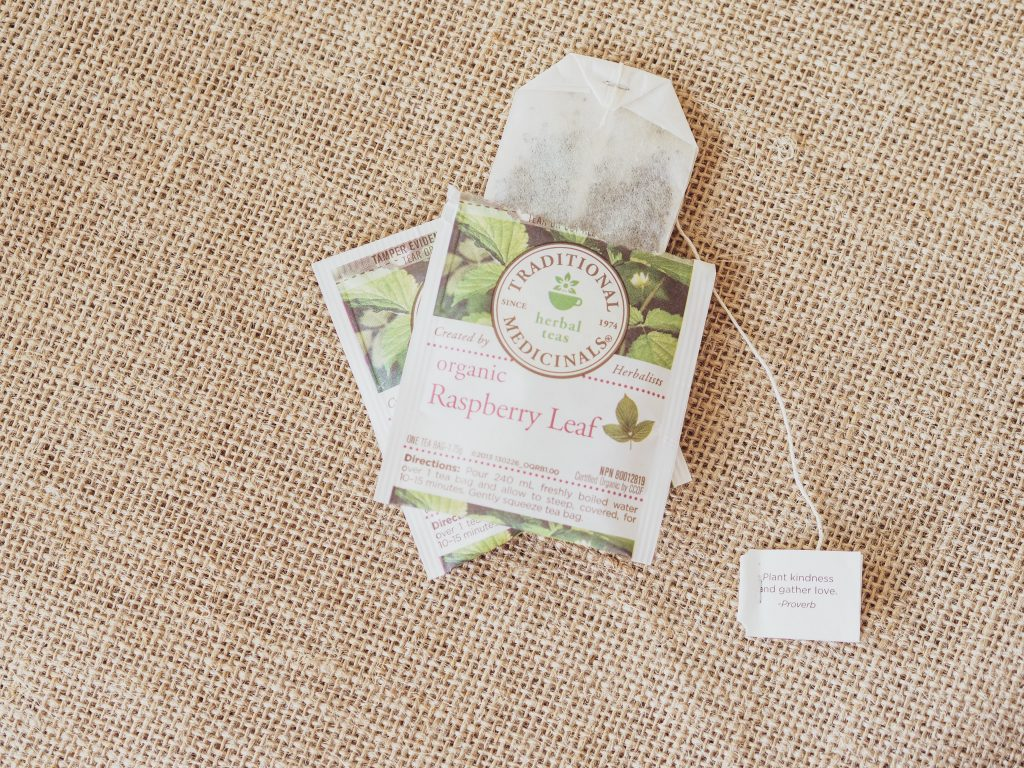 Two overlapping Traditional Medicinals Herbal Teas Organic Raspberry Leaf tea packets with one of the tea packets open, exposing the tea bag inside.