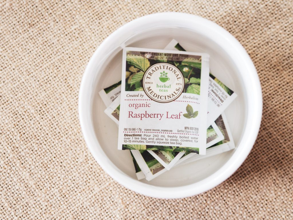 A stack of Traditional Medicinals Raspberry Leaf Tea packets stacked on top of each other in a white glass bowl