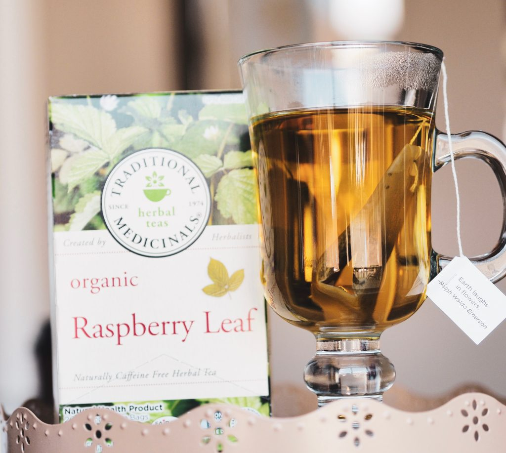 Box of Traditional Medicinals Herbal Teas organic raspberry leaf tea on a tray with a teacup filled with hot tea steeping inside