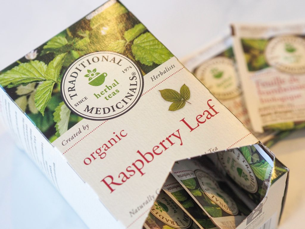 Box of Traditional Medicinals Herbal Teas Organic Raspberry Leaf Tea with two tea packets in the background