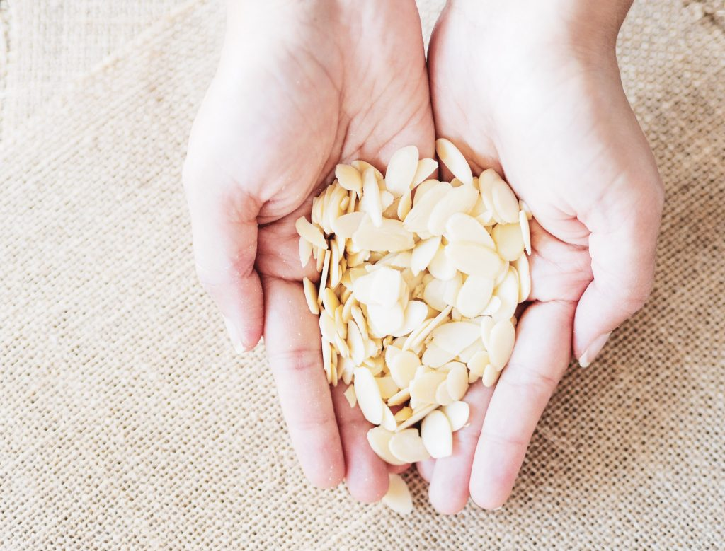 A pair of hands holding a small amount of slivered almonds