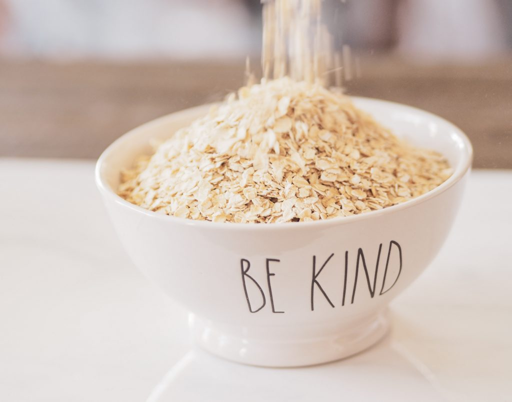 Uncooked rolled oats being poured into a bowl with the words be kind on it