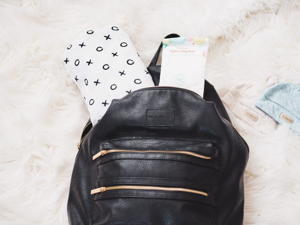 Black backpack with baby blanket and baby wipes spilling out of the bag and two newborn baby hats beside the backpack diaper bag