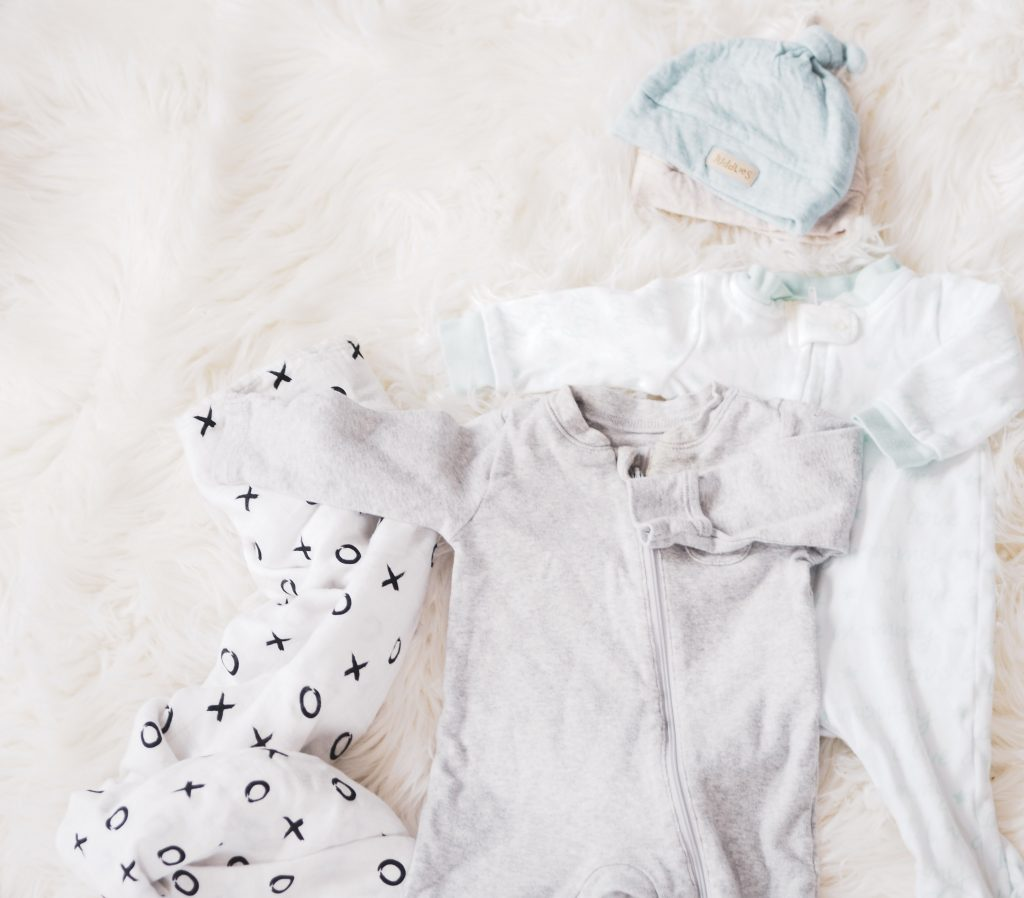 Two baby sleepers with zippers, one grey and one white, layered on top of each other, with one baby blanket underneath with xoxo print, and one blue and one beige newborn baby hat layered on top of each other