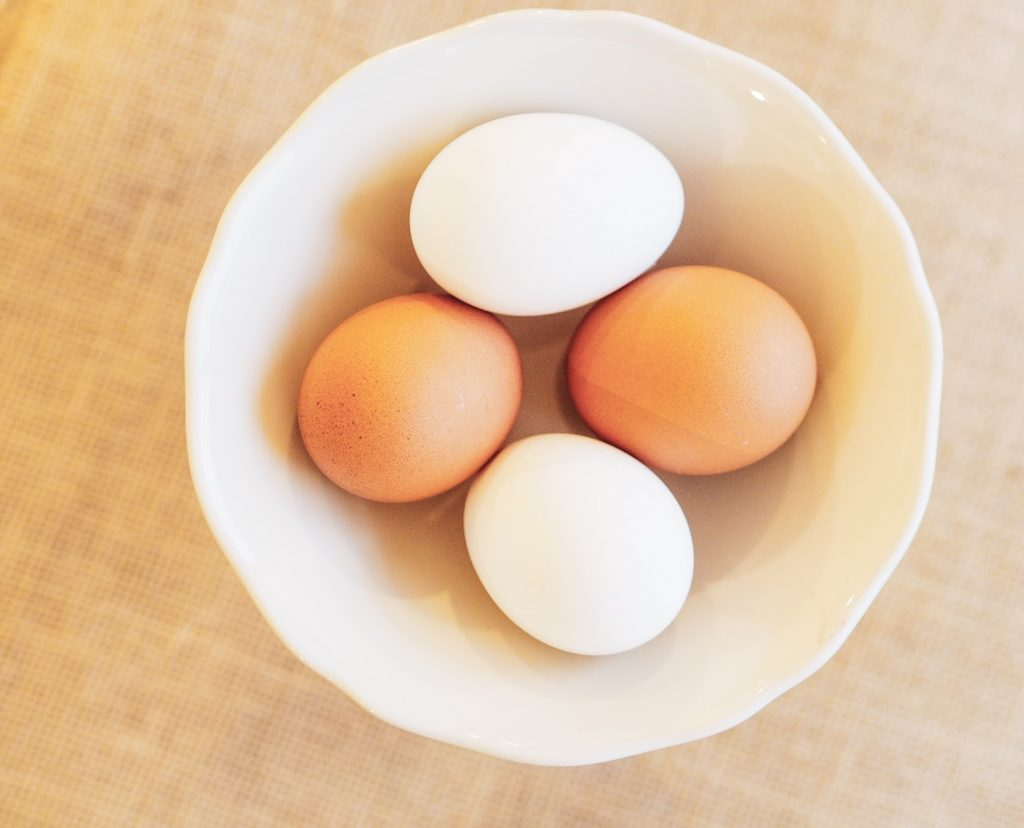 Four eggs in a bowl, two white eggs, two brown eggs