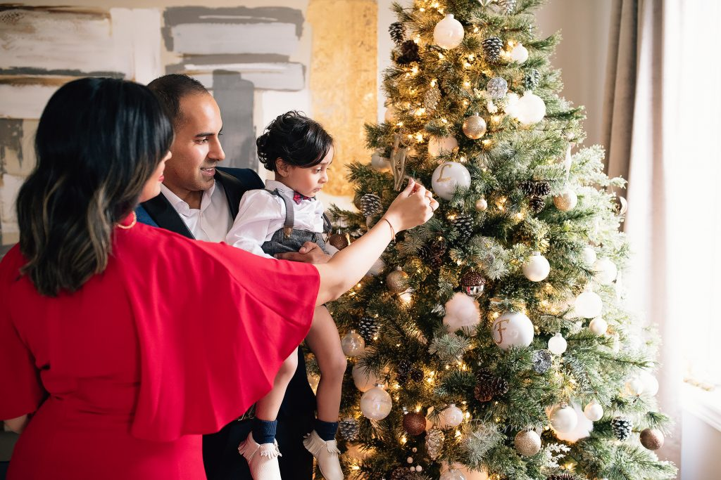 Mom, Dad and Baby putting ornaments on Christmas Tree