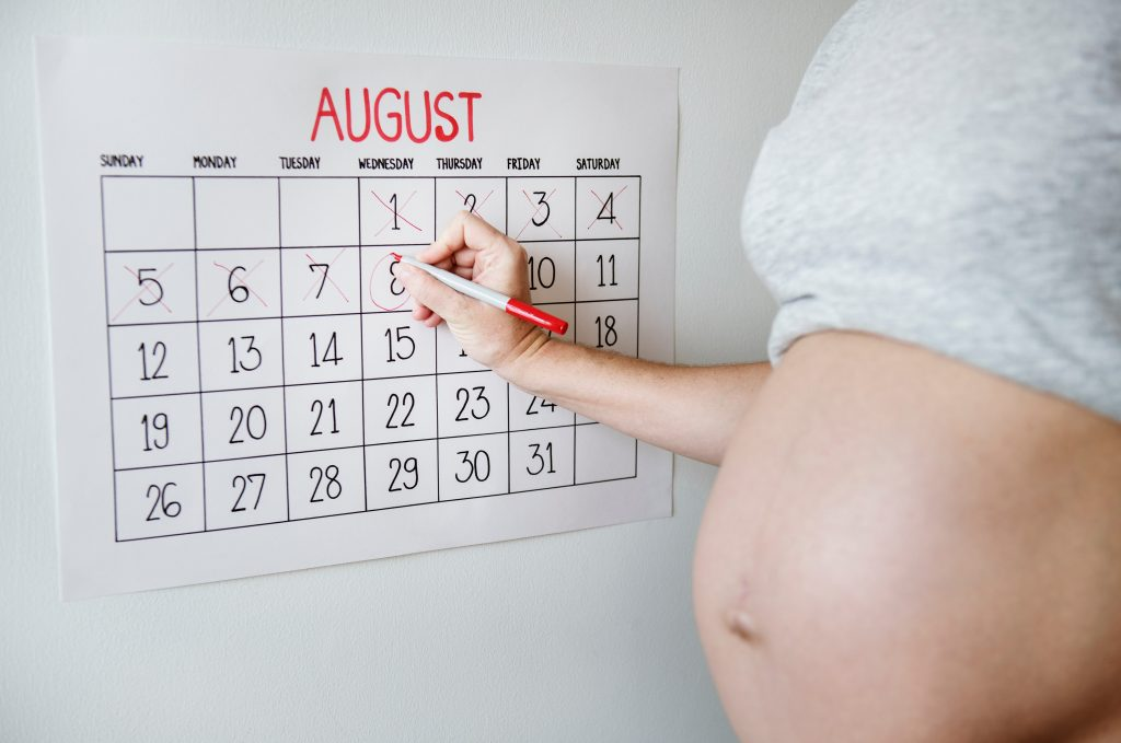 Pregnant woman marking dates on August calendar