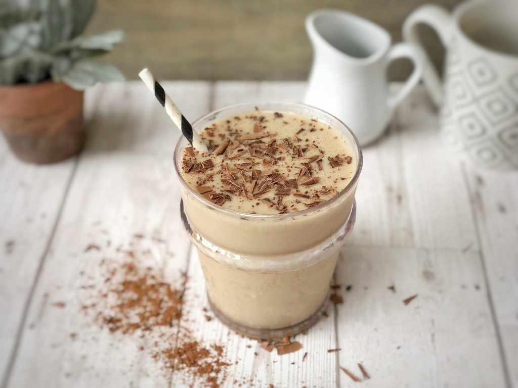 Smoothie on a table with a straw and chocolate shavings as a garnish