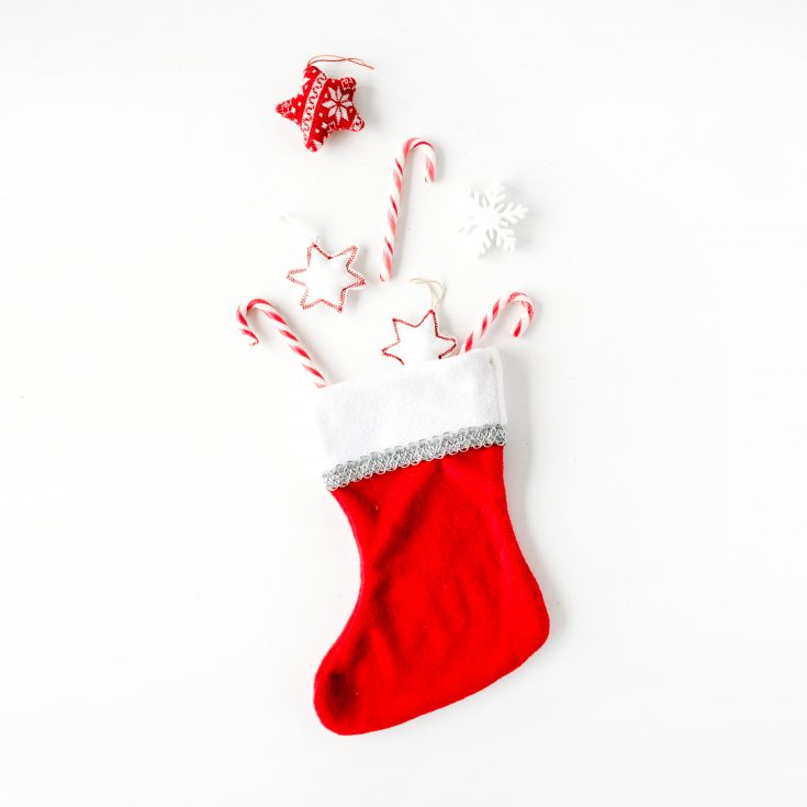 creative arrangement of bright red christmas toys and stocking stuffers in christmas stocking on white background. flat lay, top view