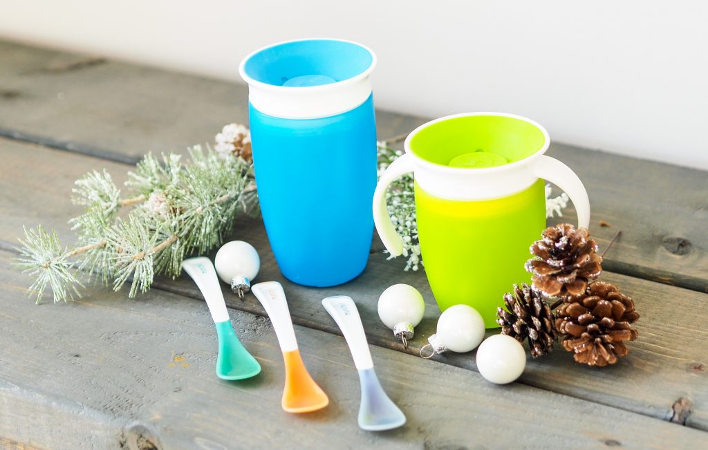 Two munchkin baby cups and three baby spoons on top of a wooden table surrounded by Christmas decorations