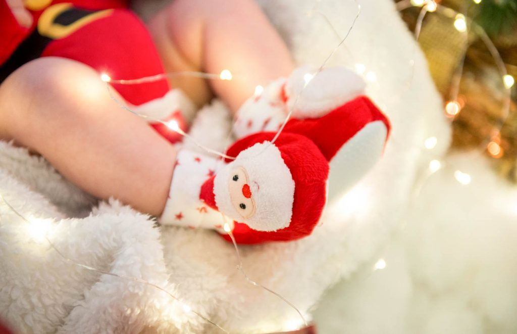 baby's feet in christmas booties surrounded by twinkling lights