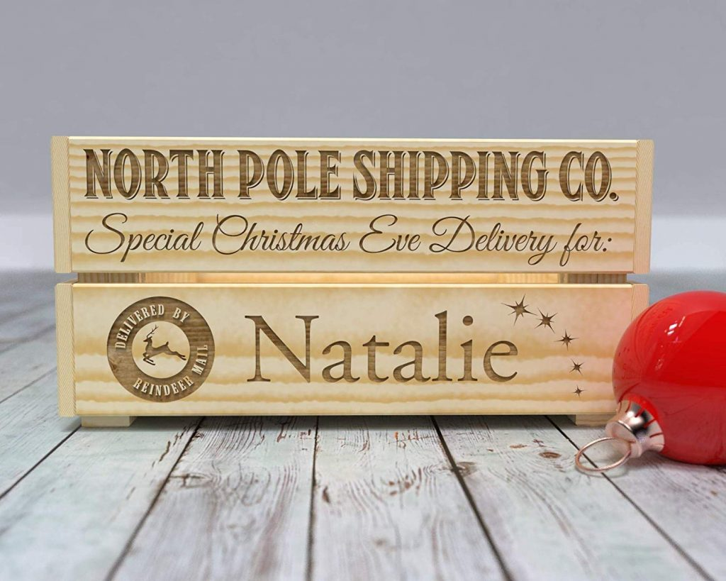 Wooden crate with North Pole shipping co special Christmas Eve Delivery for Natalie engraved on it, with a red ornament on the side