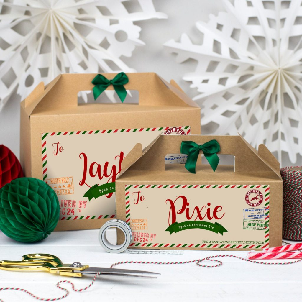 two Christmas parcel box with decorations and golden scissors in front of the boxes